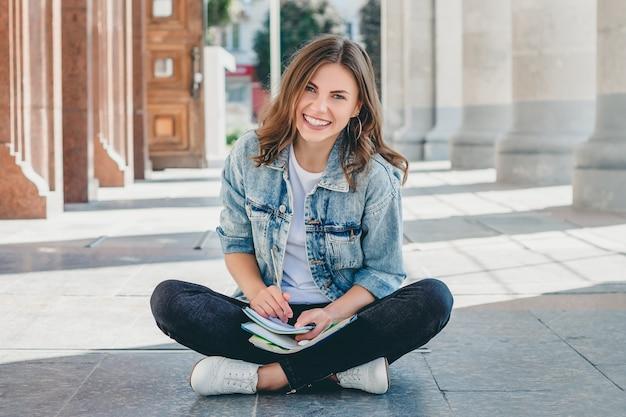 女子学生は大学の反対側に座って笑顔します。かわいい女子学生は、ペンシル、フォルダー、ノートブックを保持し、笑います。女の子がレッスンを教える