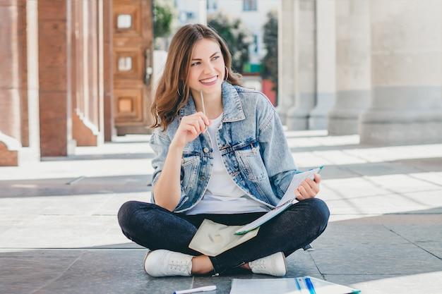Девушка студентка сидит напротив университета и улыбается. милая девушка студент держит карандаши, папки, тетради и смеется. девушка преподает уроки