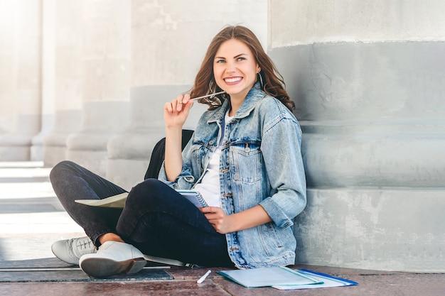 女子学生が大学の近くに座って、笑顔します。かわいい女子学生は、フォルダー、ノートブック、笑いを保持しています。女の子がレッスンを教える
