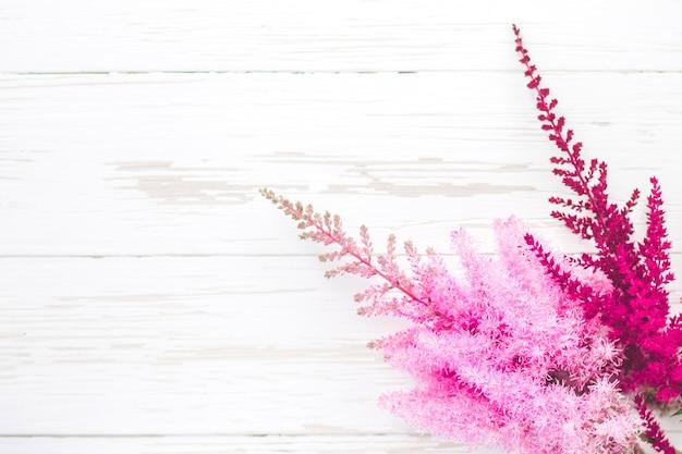 白い木製の背景に明るい新鮮な赤とピンクの花