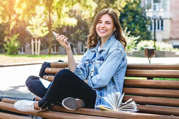 若い女子学生は公園のベンチに座って、携帯電話を保持しています。女の子は公園でオーディオブックを聴きます。