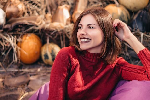 カボチャと笑顔の背景に座っている若い女の子