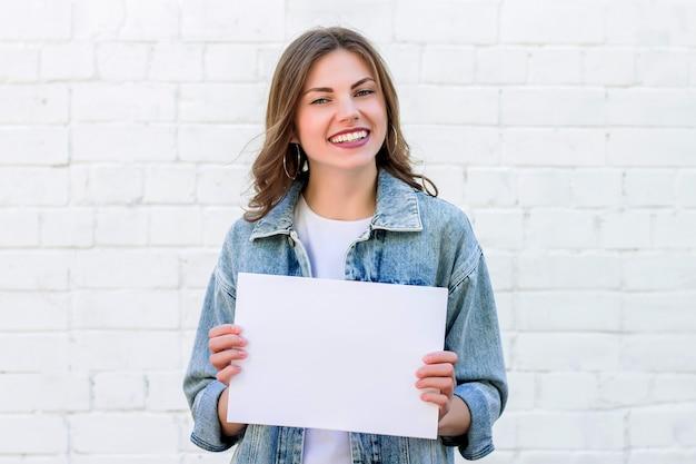 笑みを浮かべて、白いレンガの壁の背景に紙の白いシートを保持している女子学生