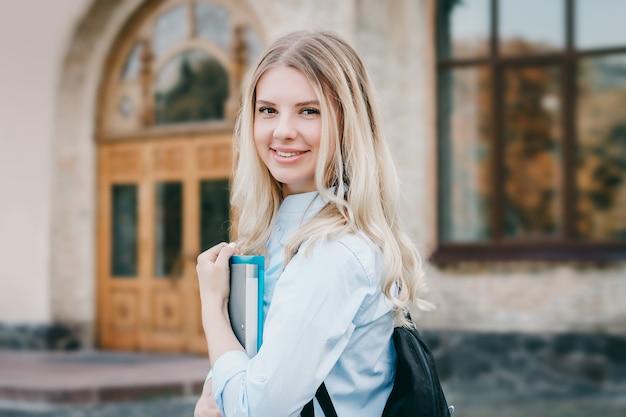 金髪の学生少女は笑みを浮かべて、大学の背景に彼女の手でフォルダーとノートを保持しています。