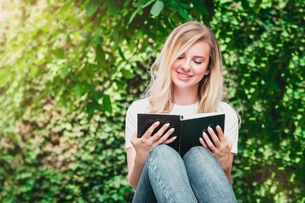 若いブロンドの女の子はベンチに座って、本を読んで、木々や茂みの背景に公園で笑顔