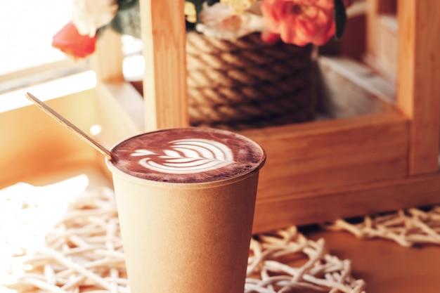 Чашка капучино с рисунком на столе в кафе