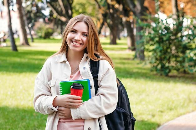 ブロンドの女子学生がノートブックとコーヒーのカップで公園を散歩します