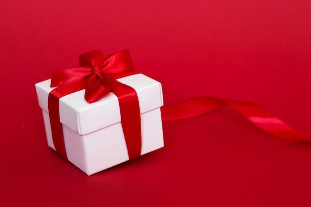 赤に赤いリボンの付いた白いボックス。グリーティングカードの概念