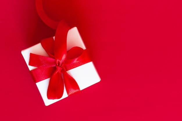 赤、トップビュー、コピースペースに赤いリボンと白いボックス。グリーティングカードの概念