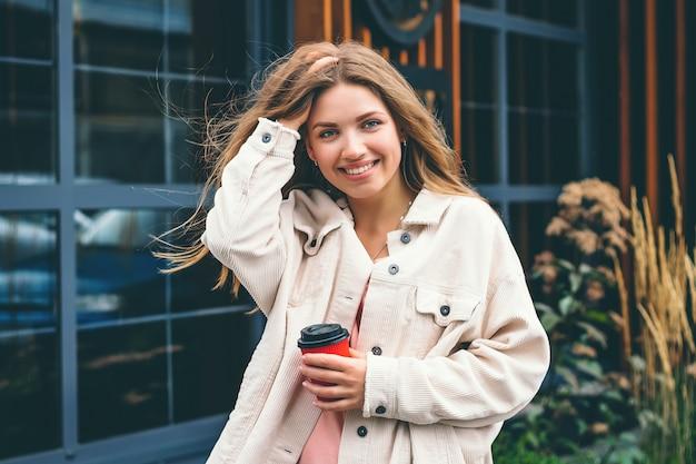 ブロンドの女の子の学生の女の子が笑顔し、街を歩き回って立っている