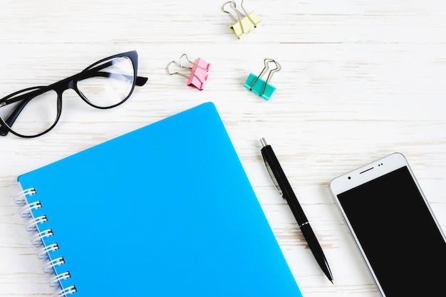 閉じたノート、ペン、メガネ、携帯電話、白い木製のテーブル、フラット横たわっていた、トップビューでコーヒーカップ。オフィステーブルデスク、職場
