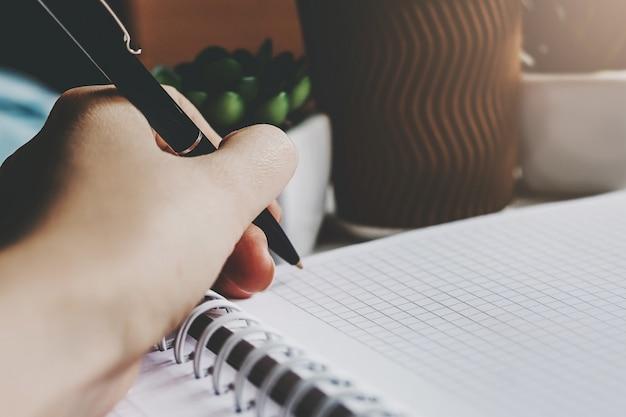 女性の手はペンを保持し、ノートに書き込みます
