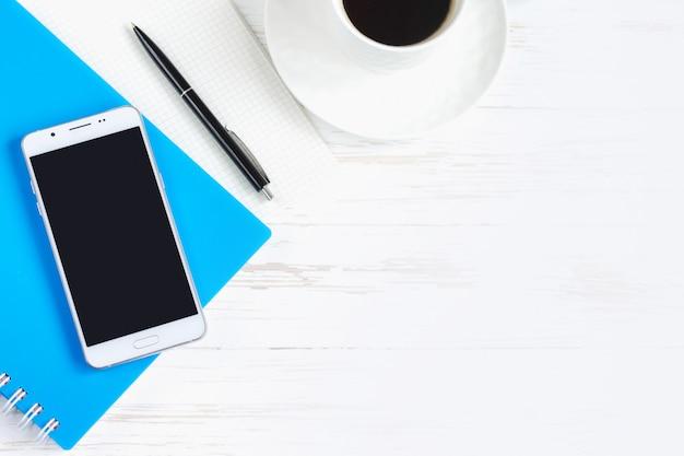 Блокнот, ручка, очки, мобильный телефон, чашка кофе на белом деревянном столе, плоская планировка, вид сверху. стол офисный стол, рабочее место