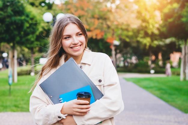 女子学生は笑顔し、ノートブックとコーヒーを飲みながら公園を散歩します。