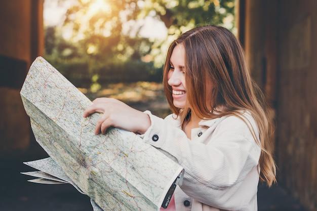 Блондинка девушка смотрит на карту. девушка студентка потерялась в городе