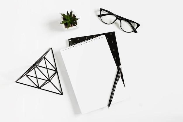 ノートブック、ペン、メガネ、白い背景に横たわる