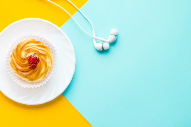誕生日の背景白い皿の上のおいしいケーキ。スペースをコピーします。上面図。黄色と青の背景