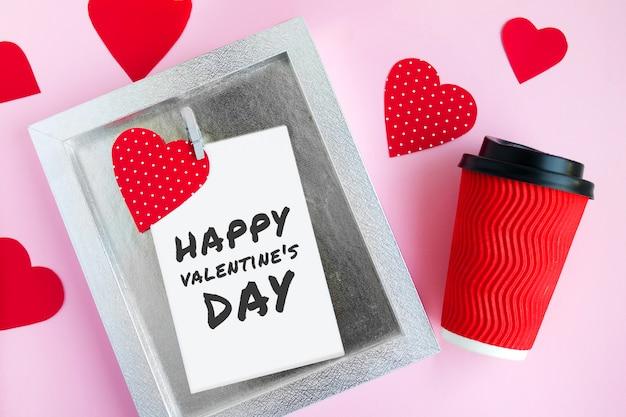 多くの赤いハート、洗濯はさみとバレンタインの碑文と明るいピンクの背景にコーヒーカップのフレーム
