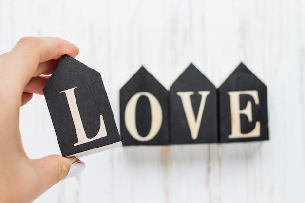 女性の手は碑文の愛と木製の数字を保持しています