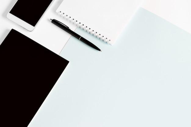 ノート、ペン、スマートフォン、オフィスツール、明るい青の背景にフラットレイアウト