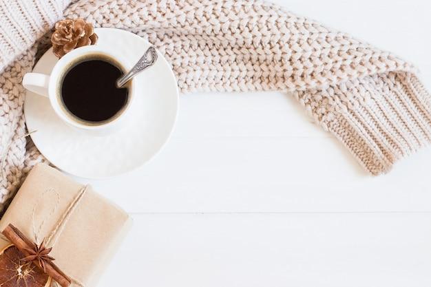 一杯のコーヒー、セーター、白い木製の背景にクラフトギフトボックス