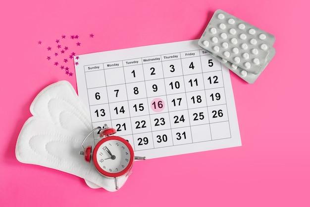 Календарь менструации с прокладками, будильник, гормональные противозачаточные таблетки. концепция менструального цикла женщины. обезболивающие при менструальной боли