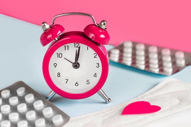 月経パッド、目覚まし時計、ホルモン避妊薬。月経期間のコンセプト。月経痛の鎮痛剤
