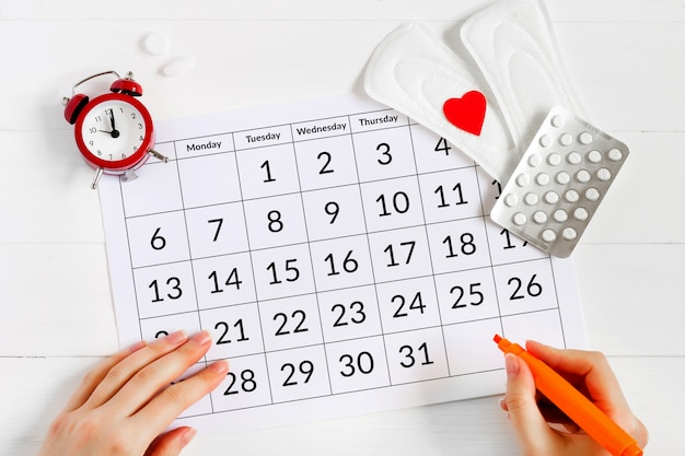 パッド、目覚まし時計、ホルモン避妊薬の付いた月経カレンダー。女性の月経周期の概念。月経痛の鎮痛剤