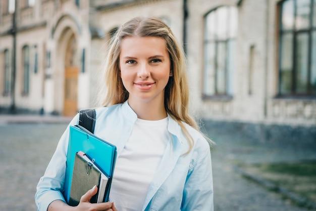 金髪の学生の女の子は笑みを浮かべて、大学で彼女の手でフォルダーとノートを保持しています。