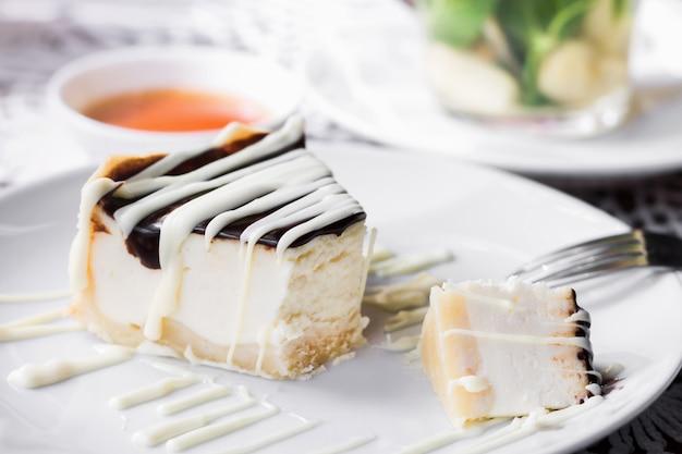 カフェの皿の上の白とダークチョコレートのチーズケーキ。