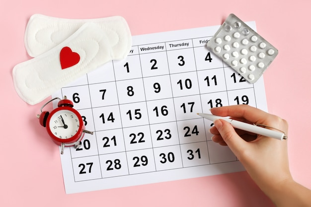 パッド、目覚まし時計、ホルモン避妊薬の付いた月経カレンダー。女性の月経周期の概念。