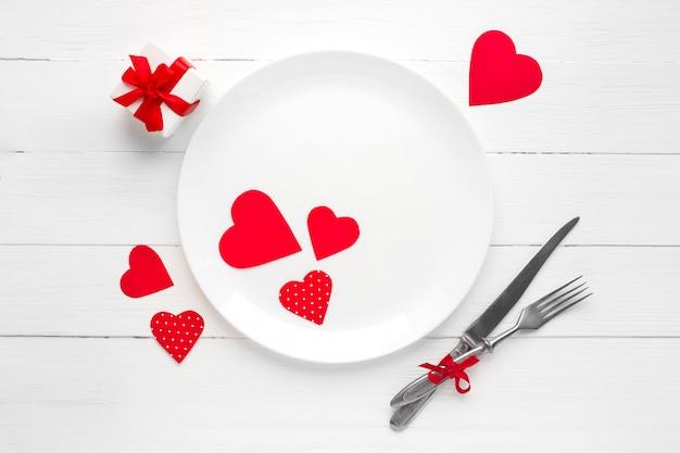 白い皿、フォーク、ナイフ、赤いリボン、白い木製のテーブルの上のギフトボックスに赤いハート