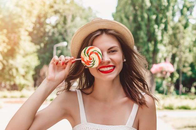 麦わら帽子とマルチカラーのロリポップの少女が公園を散歩します。彼女の手にお菓子と夏の公園で笑っている女の子