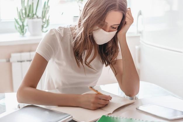 Девушка с апатией и депрессией в медицинской маске удаленно работает дома и садится за стол, пишет в блокноте. студентка учится на дому, изолировать карантин, остаться дома концепции