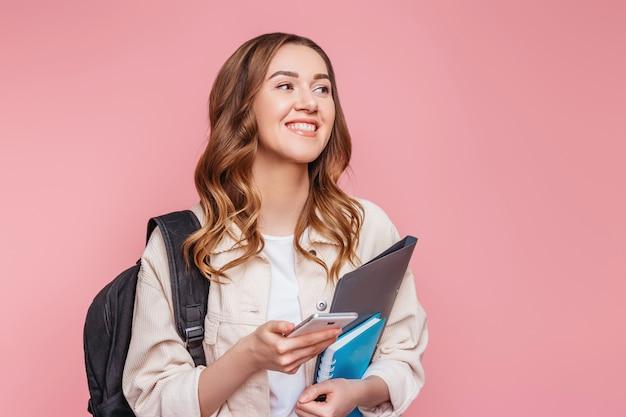 ピンクの壁に分離された離れて見て、彼女の手で携帯電話を持って笑っている笑顔の女子生徒。バックパックのメモ帳のノートを持つ若い女性は面白いメッセージを読み取ります