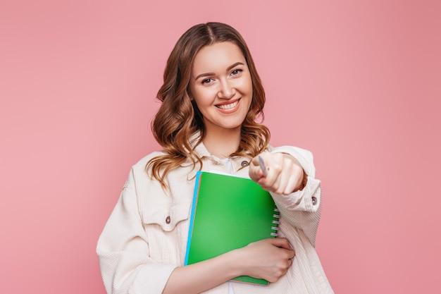 学生の女の子のフリーランサーは笑顔でピンクの壁に分離された自分の前でカメラに指を向けます。会社の従業員を笑いながらノートを持つ幸せな若い女性