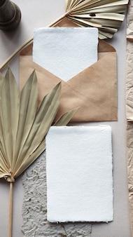 織り目加工のテーブル背景に乾燥ヤシの葉とクラフト封筒と空白の白い結婚式招待状のモックアップ。ブランドアイデンティティのエレガントでモダンなテンプレート。トロピカルなデザイン。フラット横たわっていた、トップビュー