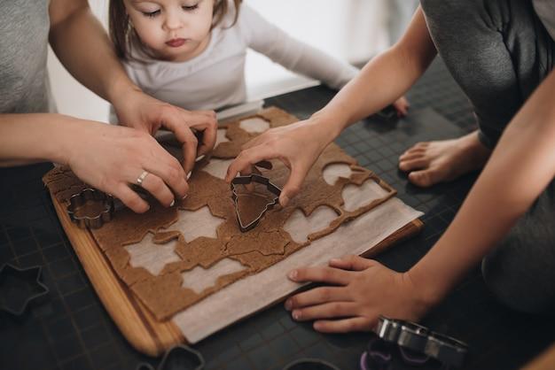 家族はキッチンでジンジャーブレッドクッキーを準備します。お父さん、お母さん、息子、娘、兄弟姉妹。こねる生地、クッキーカッター、新年、クリスマス、休日のディナー。グレーのホームウェア。