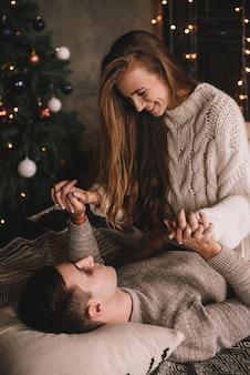 寝室のベッドをカップルします。暗いインテリア。正月とクリスマス。抱擁とキス。愛。白いセーターとハイソックス。ロマンチックな会議。デート愛好家。