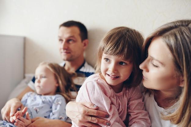 Дети и родители отдыхают утром в постели. дети балуются, обнимаются. двойняшки. две дочери.