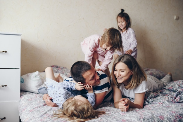 Дети и родители отдыхают утром в постели. дети балуются, обнимаются. двойняшки. дерево дочки.