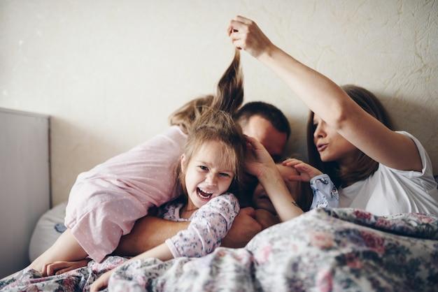 Дети и родители отдыхают утром в постели. дети балуются, обнимаются. двойняшки. три дочери