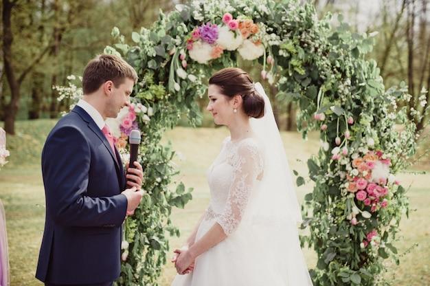 Классическая свадьба весной. церемония. жених произносит обещание и держит кольцо в руке.