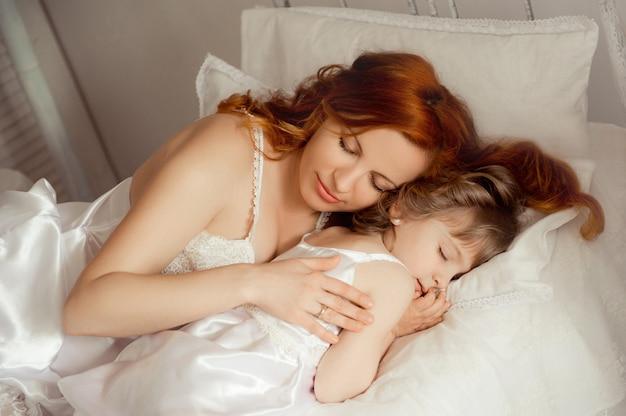 ママは娘の隣で眠ります。眠っている赤ちゃん。