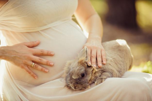 Легкое прозрачное платье. в ожидании чуда. беременная девушка поглаживает серого кролика.