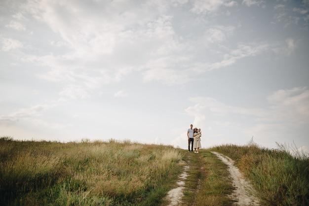 Семья, мама, папа, дочь гуляют на холме в поле. мама и дочка в желтых одинаковых платьях.
