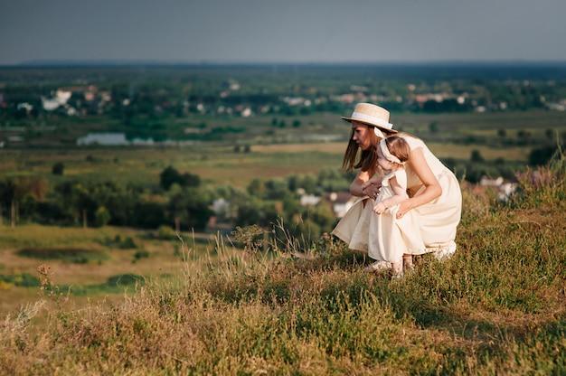 Семья, мама, дочка гуляют на холме в поле в желтых одинаковых платьях.