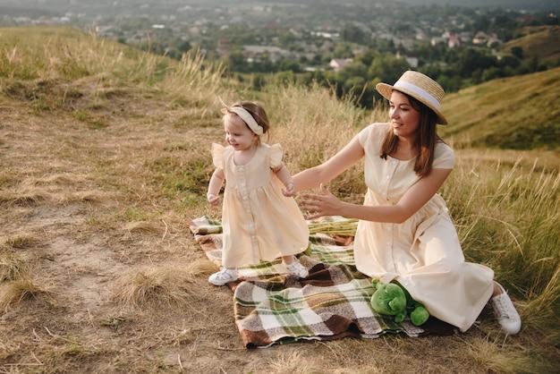 Семья, мама, дочка гуляют на холме в поле в желтых одинаковых платьях. ребенок убегает от мамы.