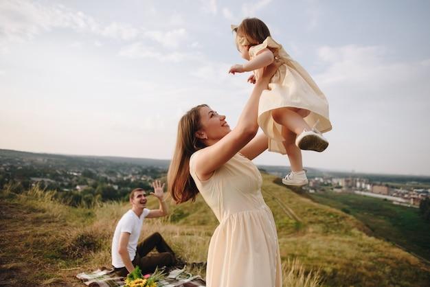 Семья, мама, папа, дочь на пикник на холме в поле. мама и дочка в желтых одинаковых платьях. подсолнухи.