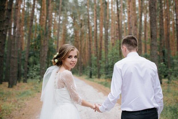 Свадебная пара в лесу. красивая невеста и жених на прогулке.